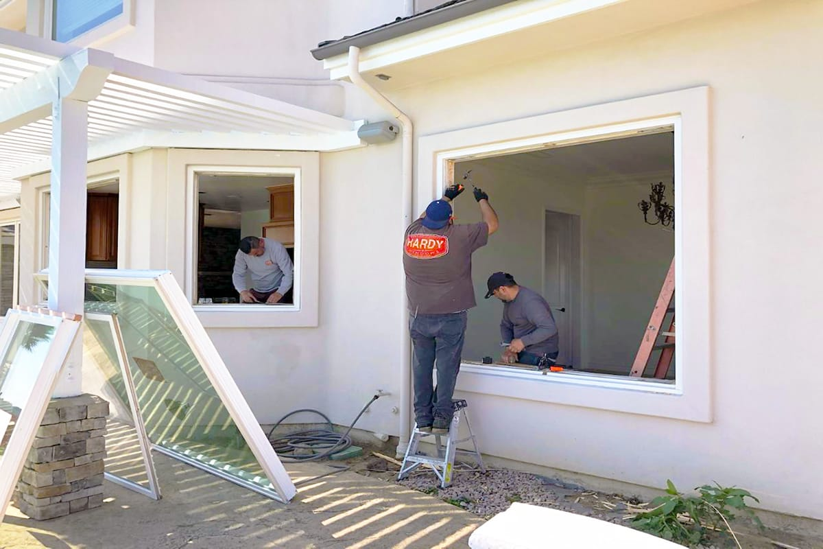 Our crew members installing a patio slider door and window in someone's residential home